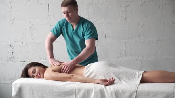 Mladý masér dělá záda Masáž tmavé mladé dívky. Masážní skolióza. Dívka dostane potěšení z relaxační masáž zad