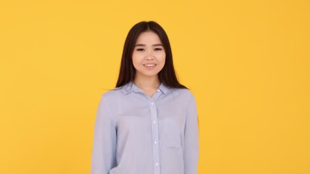 Asian girl shows symbol of love. showing heart with hands on yellow background