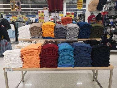 CHIANG RAI, THAILAND - NOVEMBER 21 : Folded colorful t-shirt sold on supermarket display shelf on November 21, 2019 in Chiang Rai, Thailand.