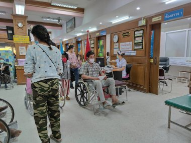 CHIANG RAI, THAILAND - MARCH 23 : Unidentified asian male patient with hygienic mask sitting on wheelchair in Phan hospital during the spread of Covid-19 virus on March 23, 2020 in Chiang Rai, Thailand.