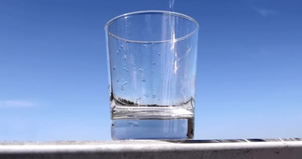 crystal glass full of water with the blue sky in the background