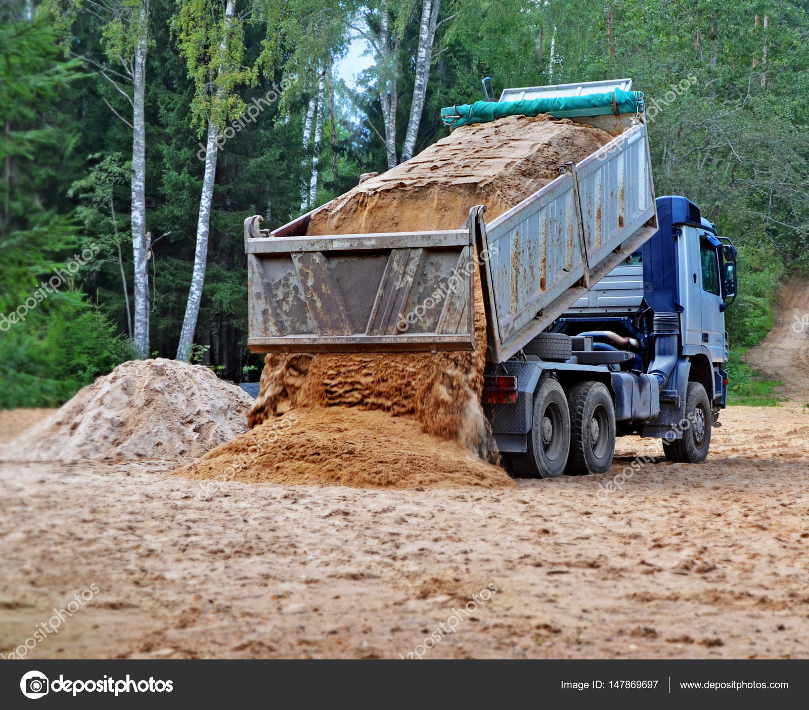 Blue Dump Truck With Hoisted Body Unloads Sand On The Building Site In Rural Areas Photo By Ann0305
