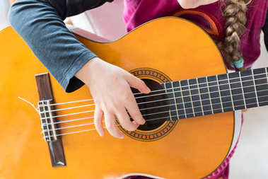Young girl playing classic guitar