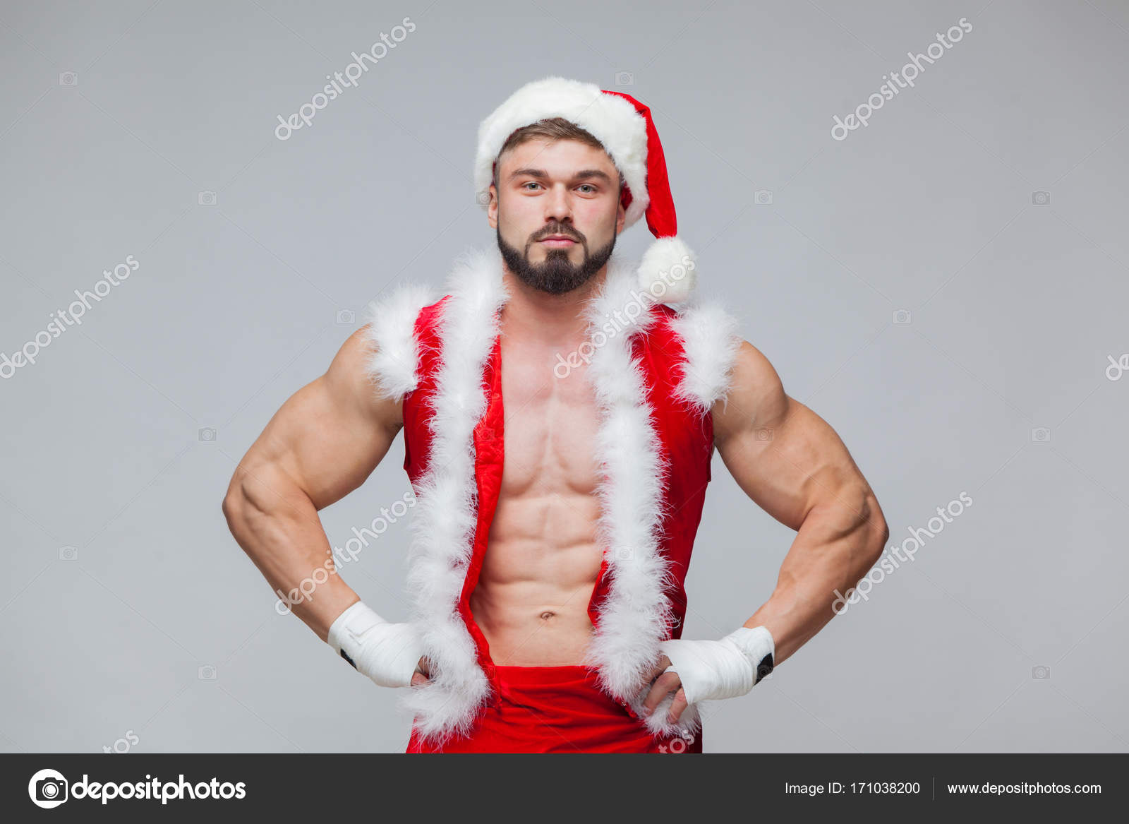 bbe0fa1485722 Christmas. Sexy Santa Claus . Young muscular man wearing Santa Claus hat  demonstrate his muscles. Muscular Fighter kickbox With white Bandages.–  stock image