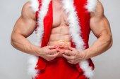 Fényképek Ünnepek és ünnepségek, újév, karácsony, sport, a testépítés, az egészséges életmód - izmos a jóképű szexi Mikulás élvezi a friss sült csővezeték forró fánk left for neki ajándékba köszönöm a