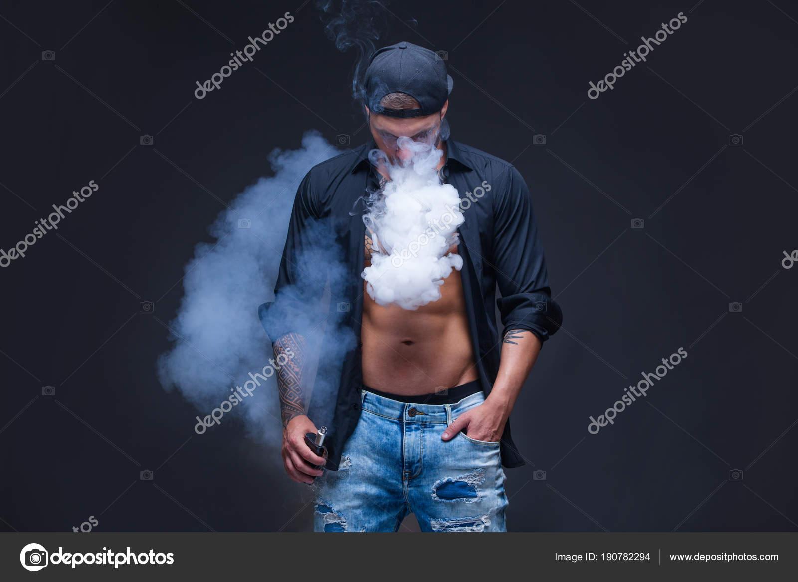 2a76e8d24b2c Vaper. El hombre vestido con vaqueros, camisa negra y gorra de ...