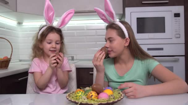 Happy easter. Two sisters eat Easter chocolate eggs. Happy family children preparing for Easter. Cute little child girl wearing bunny ears on Easter day.