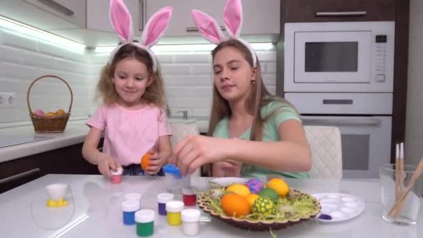 Veselé Velikonoce. Dvě sestry malují velikonoční vajíčka. Šťastné rodinné děti se připravují na Velikonoce. Roztomilé malé dítě dívka nosí králičí uši na velikonoční den.