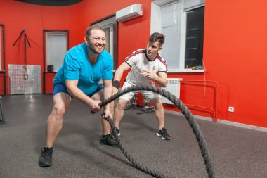 Fat young man is performing battle rope exercise in the fitness gym with the last of his strength under control of his personal coach. Excess weight