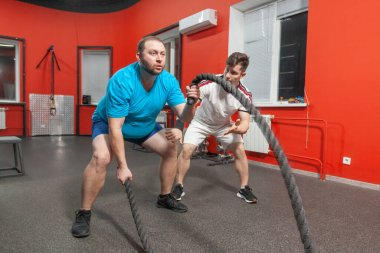 Fat young man is very concentrated performing battle rope exercise in the fitness gym under control of his personal coach. Excess weight