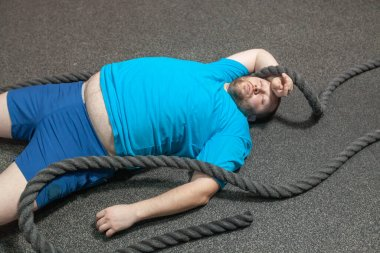 Overweight man is lying on the floor exhausted after performing battle rope exercise in the fitness gym