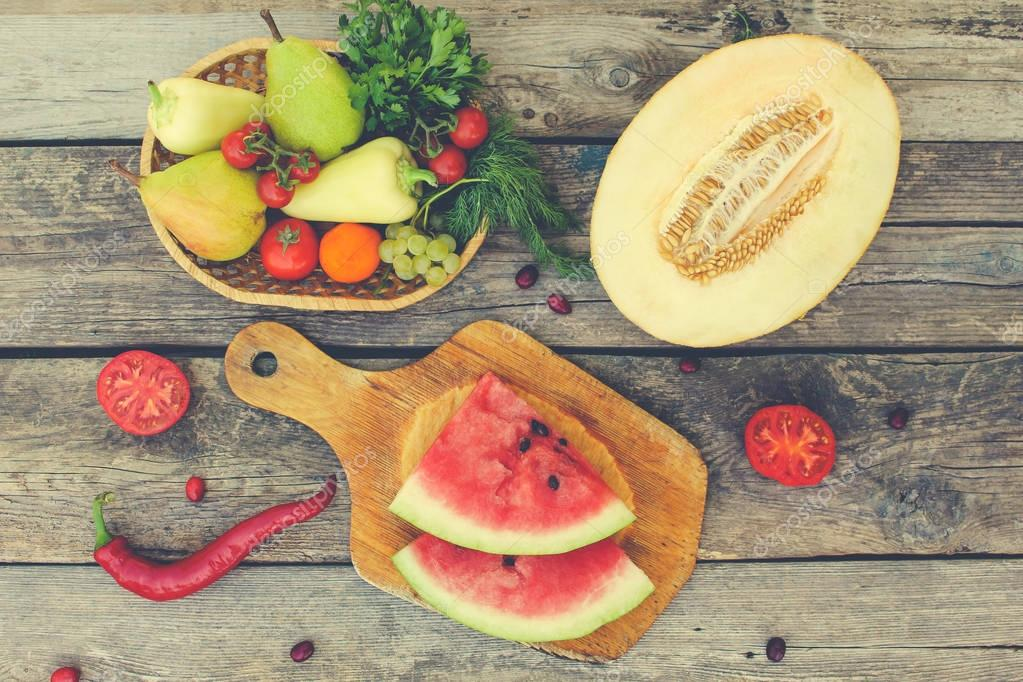 Fruits, vegetables on wooden background. Toned image.