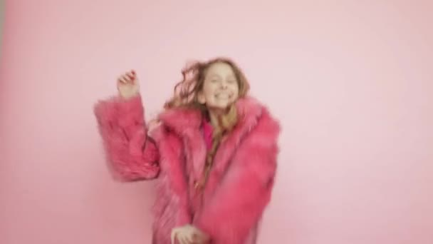 A young girl with long hair is dancing in a pink coat on a pink background.