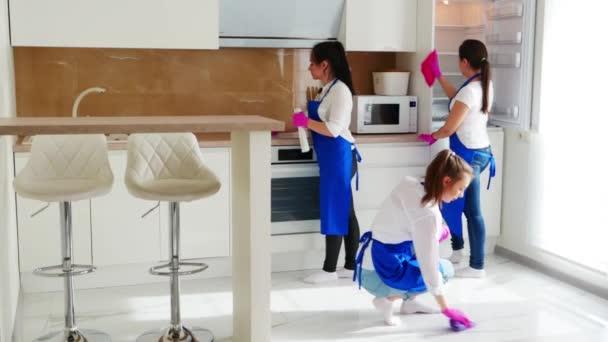 Pečlivé čištění kuchyňských skříněk. Otřete skvrnu růžovými rukavicemi na čištění. Profesionální čištění.