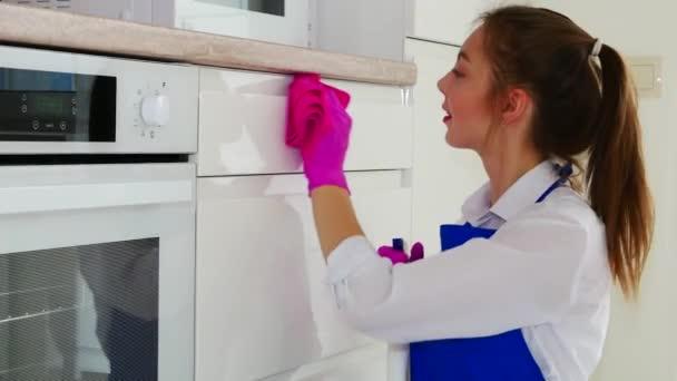 Vyčistěte místnost, otřete bílý povrch růžovými rukavicemi a růžovým hadrem. Bruneta dívka s rtěnkou dělá úklid.