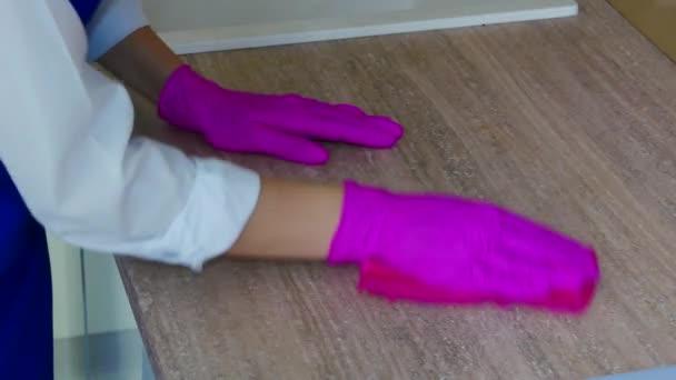 Pečlivé čištění kuchyňských skříněk. Otřete skvrny v růžových rukavicích pro čištění.