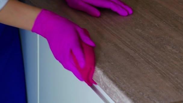 Důkladné čištění kuchyňských skříněk, mytí bočního povrchu skříně. Otřete skvrny v růžových rukavicích pro čištění.