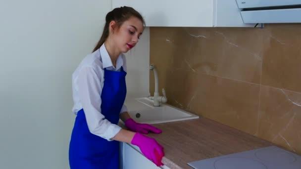 Krásná mladá dívka utírá skvrnu v růžových rukavicích pro čištění. Důkladné čištění kuchyňských skříněk, mytí bočního povrchu skříně
