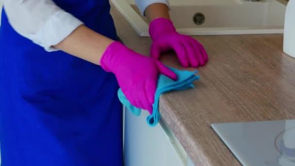 Důkladné čištění kuchyňských skříněk, mytí bočního povrchu skříně. Otřete skvrny v růžových rukavicích pro čištění