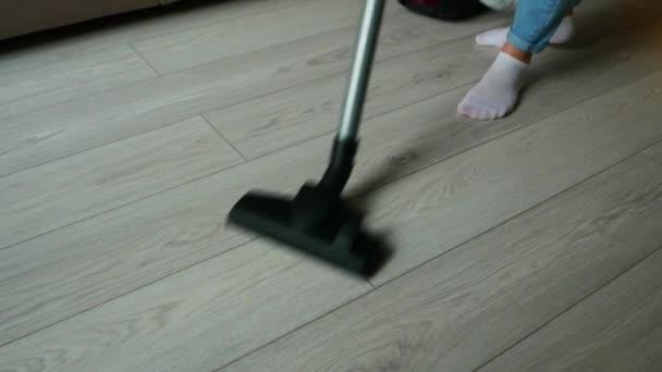 Zugeschnittenes Bild eines Mädchens in blauen Jeans, das putzt und die Holzoberfläche des Fußbodens saugt