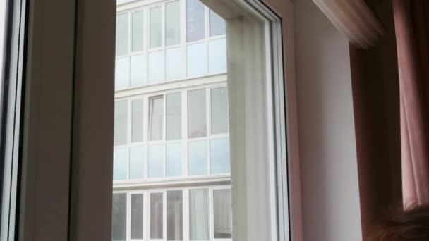 Closeup dívka myje okno se speciálním kartáčem pro čištění oken.