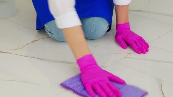 Dívka poklekne a otře podlahu purpurovým hadrem v růžových rukavicích.