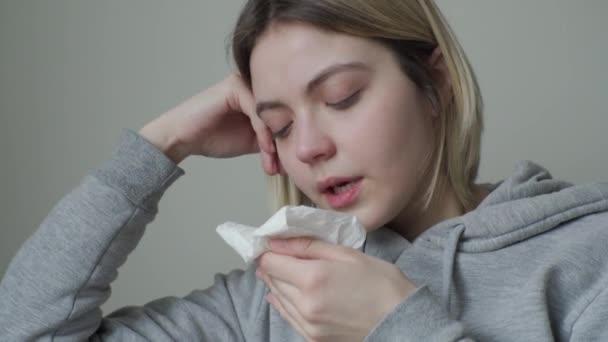 Ein Mädchen mit müden Augen ist krank und niest, aber lacht und verliert nicht den Mut. Symptome von Orvi, Coronovirus, Grippe, akuter Atemwegserkrankung, Allergie.