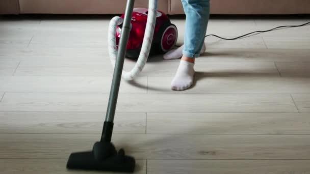 Oříznutý obraz dívky v modrých džínách, která čistí, vysává dřevěný povrch podlahy červeným vysavačem.
