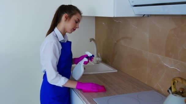 Ein brünettes Mädchen in weißem Hemd und blauer Schürze putzt die Küche mit einem Waschmittel.