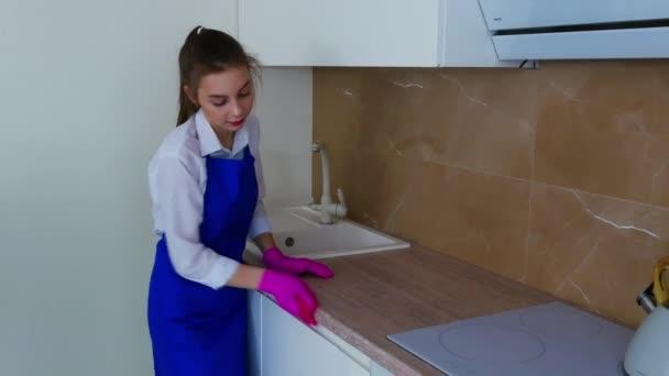 Krásná mladá dívka utírá skvrnu v růžových rukavicích pro čištění. Důkladné čištění kuchyňských skříněk.