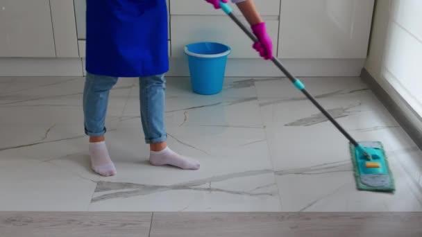 Zugeschnittenes Bild eines Mädchens in blauer Schürze und blauer Jeans, das mit einem blauen Wischmopp putzt. Ein Eimer steht in der Nähe.