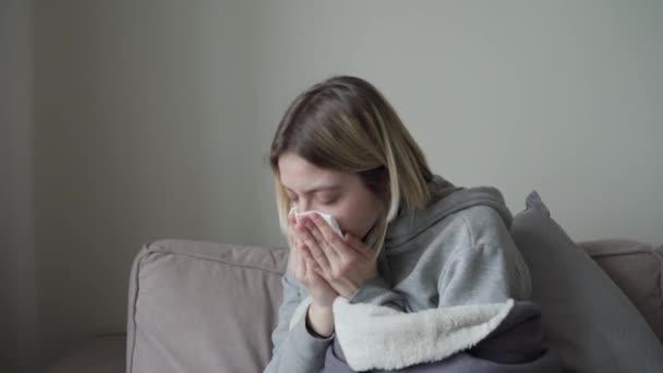 Nahaufnahme. Das blonde Mädchen mit den kurzen Haaren sitzt in vollem Wuchs, in eine Decke gehüllt, ist krank und niest in ein Einmalhandtuch. Symptom von Orvi, Coronovirus, Grippe, akuter Atemwegserkrankung.