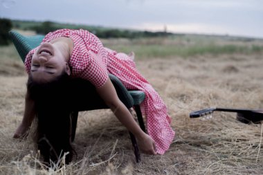 Portrait of a beautiful young, multiethnic race girl, sitting in a vintage chair, upside down, in a field with a guitar. In pasnurnuyu weather
