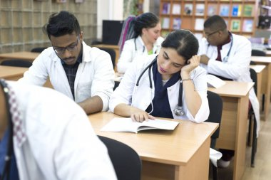 a group of young multiethnic races, medical students. Read textbooks while sitting at a desk. Dullness of exams, study