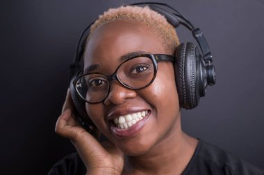 portrait of african girl listening to music on headphones, smiling.