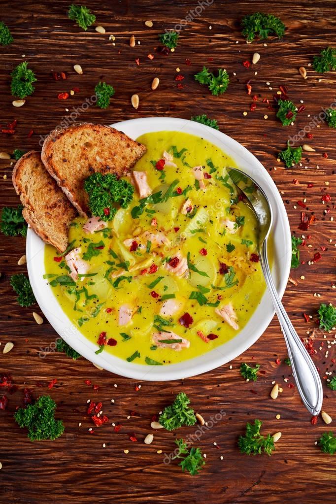 Creamy fish Salmon, leek, potato soup on wooden background