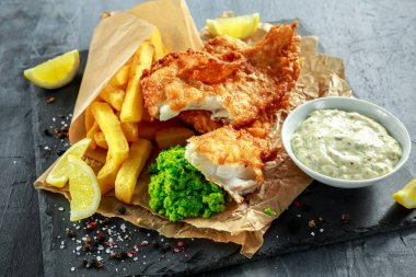 British Traditional Fish and chips with mashed peas, tartar sauce on crumpled paper.