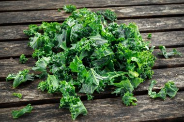 Fresh green healthy superfood vegetable kale leaves on wooden rustic table