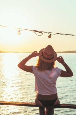 Young woman enjoying sunset at seaside
