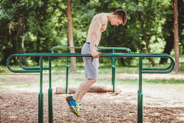 Young fit man doing push ups on bars