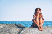 Mladá žena sedící na skále se těší opalování u moře
