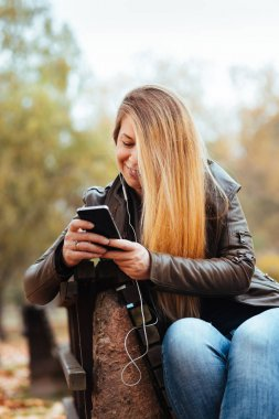 Young woman enjoying listening to the music on her smartphone in the park in autumn