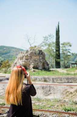 Young female traveler taking a photo of ancient ruins in Tuscany, Italy