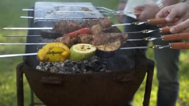 Kluci připravují grilování na grilu, rodina venku, piknik, komunikace o životě, pití vína