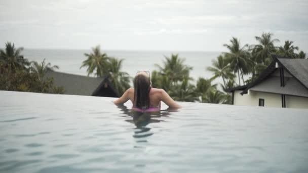 sexy Mädchen schwimmt im Pool, entspannt, in einem Badeanzug mit einer sehr schönen Figur