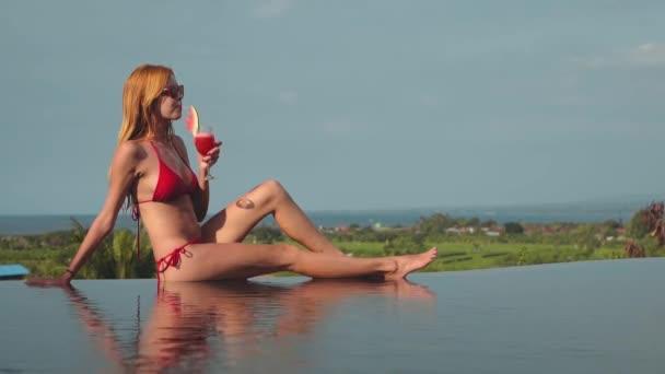 Young woman in red bikini drinking juice on edge of infinity pool, ocean view