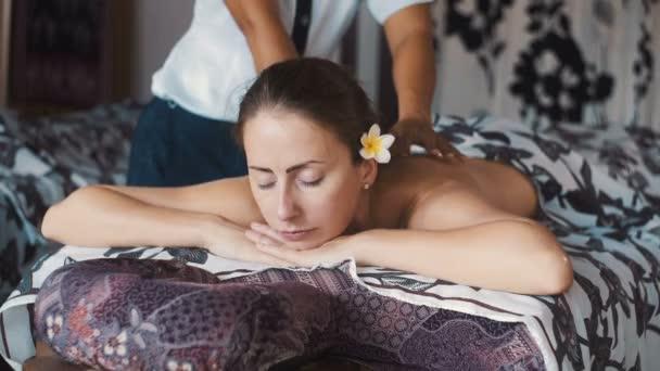 Caucasain žena s masáž zad pomocí balinéskou masérka