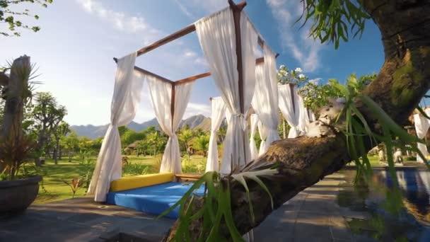 Luxusní lehátka s bílými závěsy nedaleko plavecký bazén, hory a keře