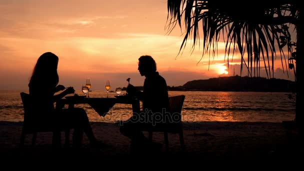 Pár siluet večeři na pláži při západu slunce