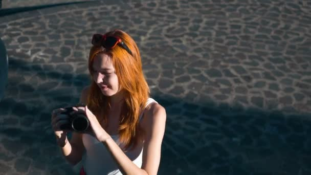 Young woman taking photo standing on paving stone